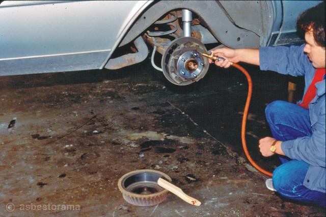 Mechanic uses air hose to remove asbestos on brakes.
