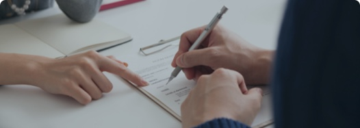Lawyer and a client signing settlement documentation