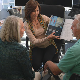 Information about mesothelioma being explained to an older couple by Karen Selby, Registered Nurse and Patient Advocate for the Mesothelioma Center.