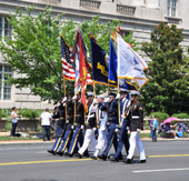 Servicemen of the National Guard marching holding flags