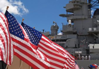 American flags in front of a U.S. Navy ship.
