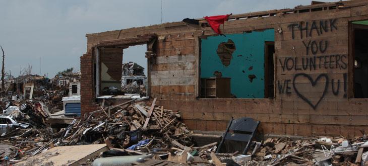 Building remnants standing among debris in Joplin, MO after a tornado.
