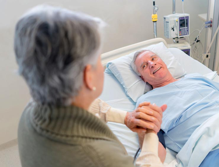 Woman comforting older man in hospital bed