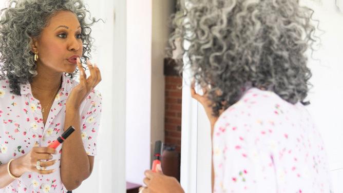 Older woman applying makeup in a mirror