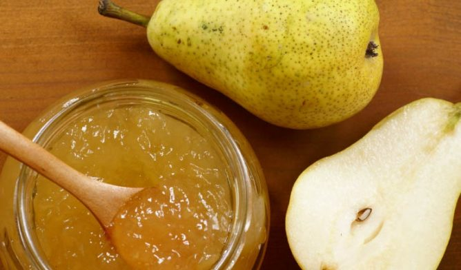 Pear jam with sliced pear on a wooden table