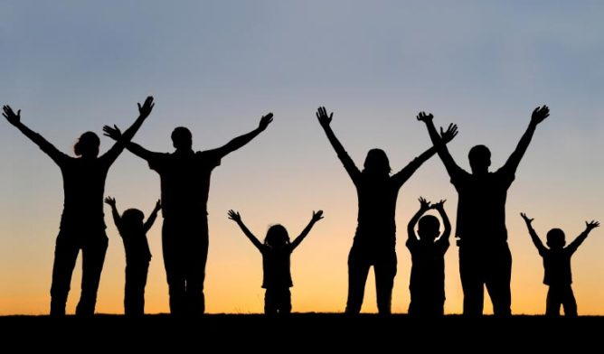 People with arms raised to the sky