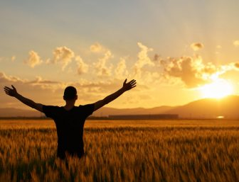 Praising the sunrise with hands in the air