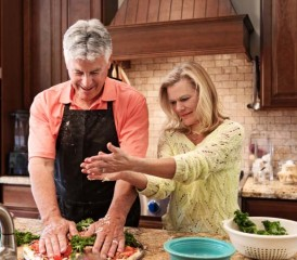 Couple prepares food together in kitchen