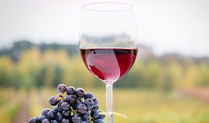Glass of red wine and bunch of grapes