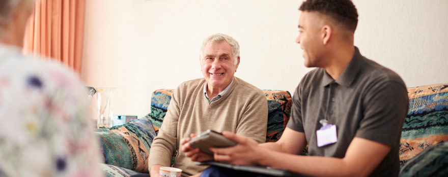 Older man speaking with a caretaker at an assisted living facility