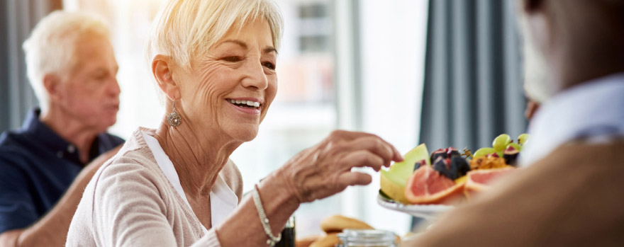 Senior-aged woman eating fruit during an event
