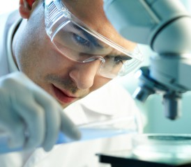 Male researcher examines sample under microscope