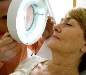 Dermatologist examining a woman's face