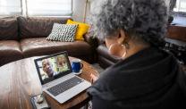 Woman looks at telehealth team on computer