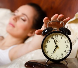 Tired woman with alarm clock