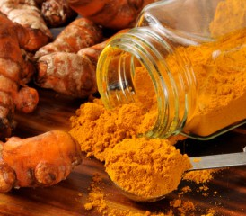 Turmeric root and powder on wood.