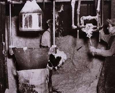 Factory workers bagging asbestos by hand
