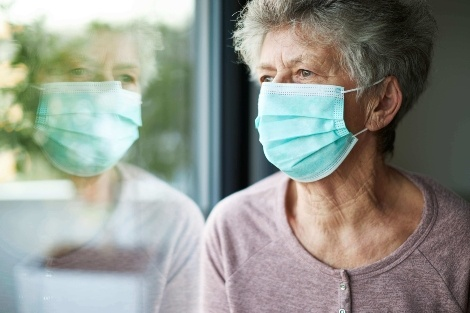 Older woman in a medical mask looking out the window