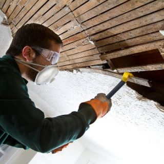 Man with mask tearing out old ceiling