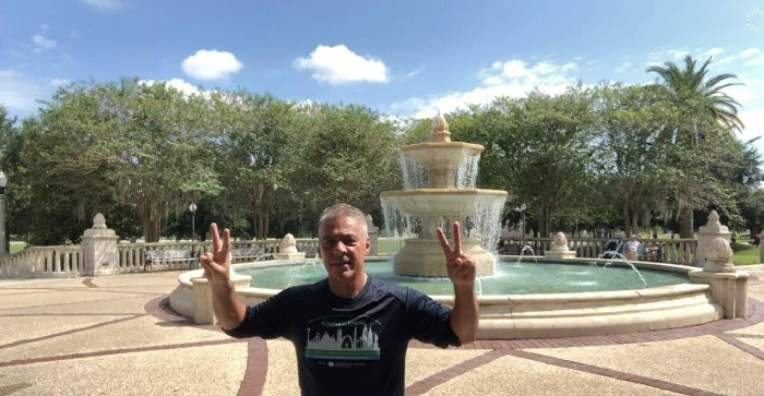 Dr. Marcelo DaSilva in front of fountain with hands raised in victory sign