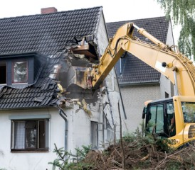 Tractor tearing down a house