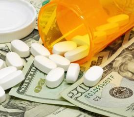 Bottle of pills spilling on money