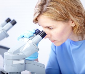 Female researcher with a microscope