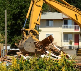 Tractor demolishing a house