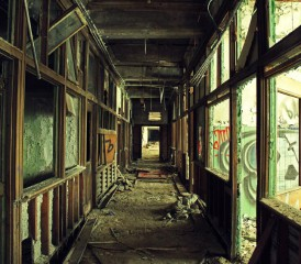 Abandoned hallway with broken glass and exposed building materials