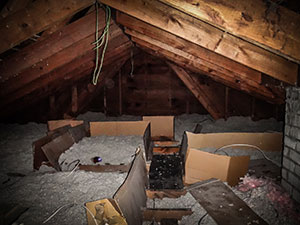 Loose insulation in a dark attic of an older home