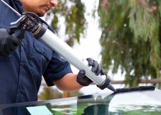 Auto mechanic repairing a glass window
