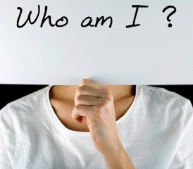 Person holding sign that says Who Am I?