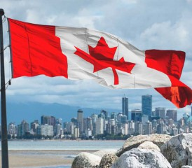 Canadian flag waving over Vancouver skyline