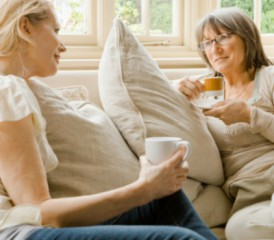 Two women sitting on couch holding coffee mugs