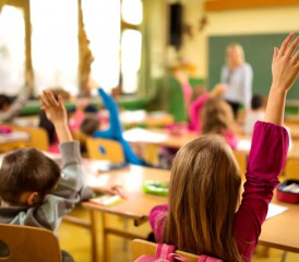 Children in a classroom with arms raised
