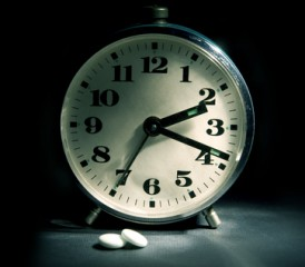 Clock with sleeping pills next to it