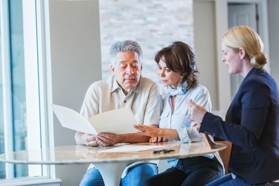 Couple looking over a document with a businesswoman