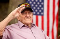 U.S. World War 2 veteran saluting with an American flag in background