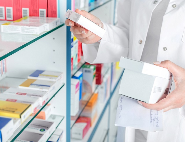 Pharmacist holding prescription and medicine