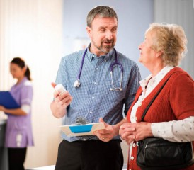 Doctor carrying clipboard talks to patient