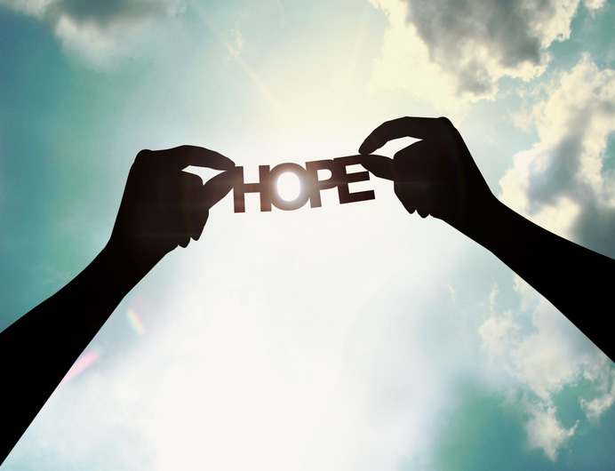 Hands holding paper cut of hope