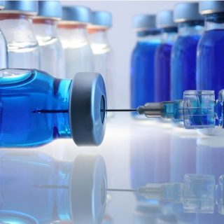 Laboratory bottles with blue content and a syringe