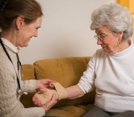 Women bandaging older woman's hand