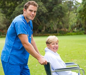 Male Caregiver Pushing Female Patient in Wheelchair