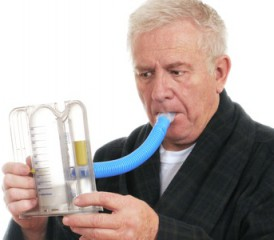 Man breathing into a lung exerciser