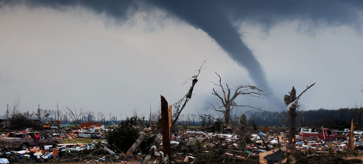 Debris along a road with the tornado shown in the background.