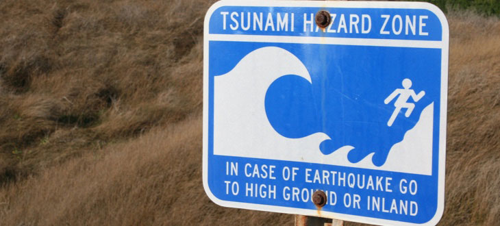 Street sign warning of tsunamis caused by earthquakes.