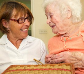 Nurse comforting an elderly woman with needlework