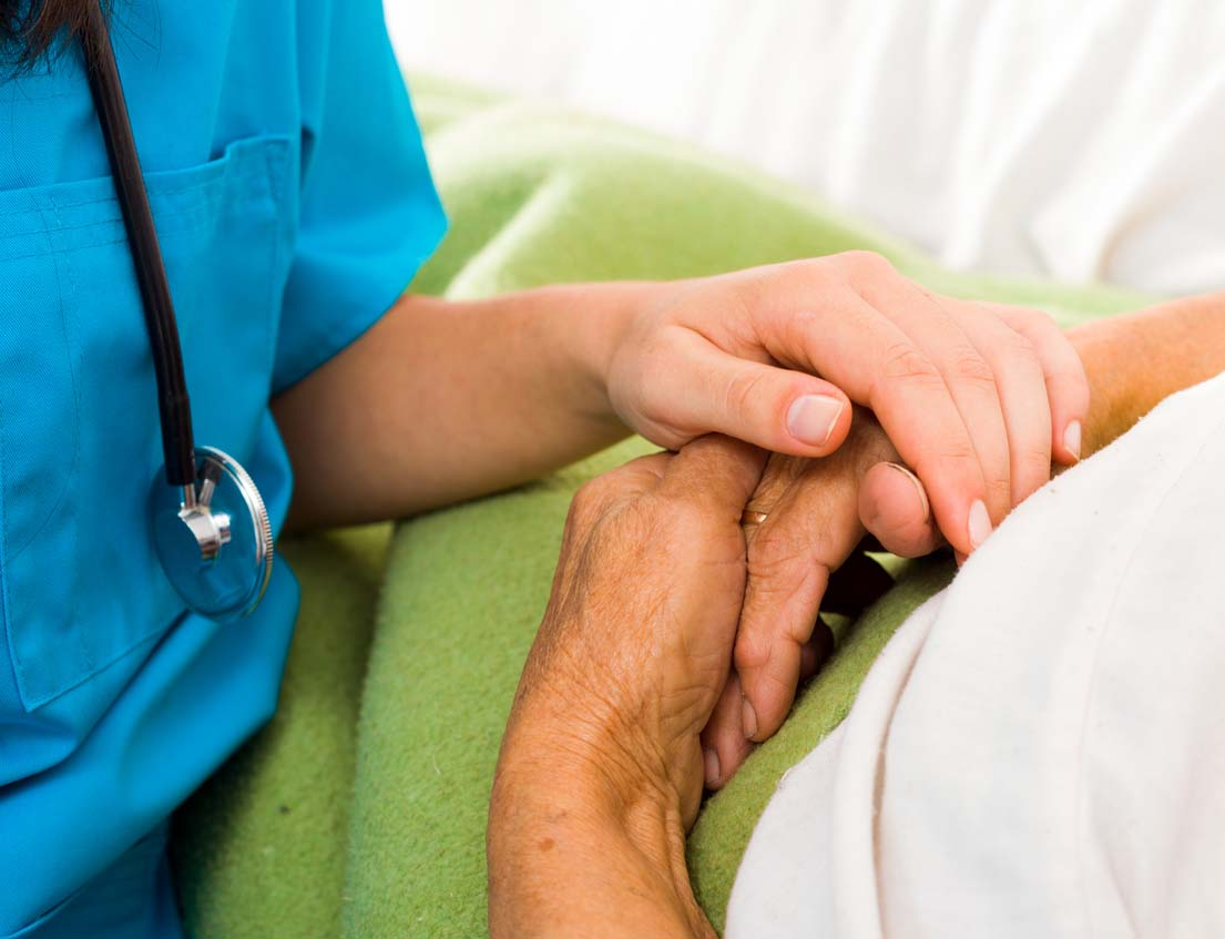 Nurse holding a patient's hands