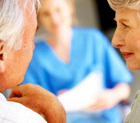 Older couple talking to a caregiver